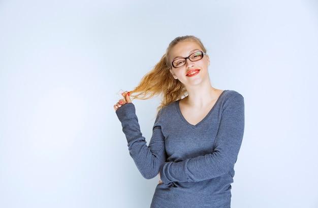 Blonde assistent met bril spelen met haar paardenstaart.
