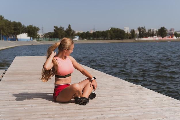Blonde atletische vrouw met lang haar die zich uitstrekt voordat ze aan een prachtig meer gaat joggen