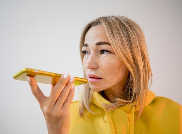 Blonde aziatische vrouw die een plak van pizza houdt