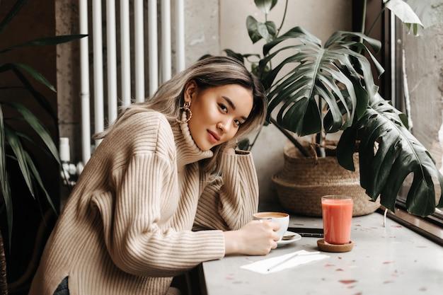 Blonde aziatische vrouw in beige oversized trui zit in café met kopje koffie en wortelsap