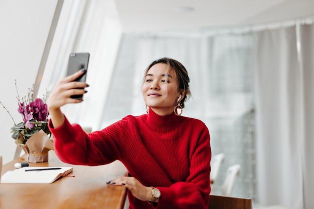 Blonde aziatische vrouw in stijlvolle oorbellen en rode trui maakt selfie tegen raam