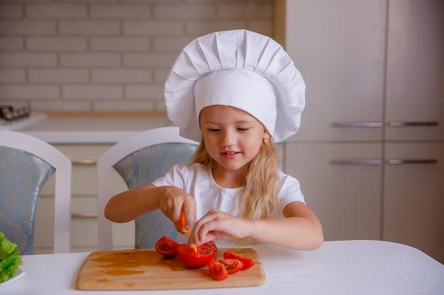 Blonde baby meisje groenten eten in de keuken