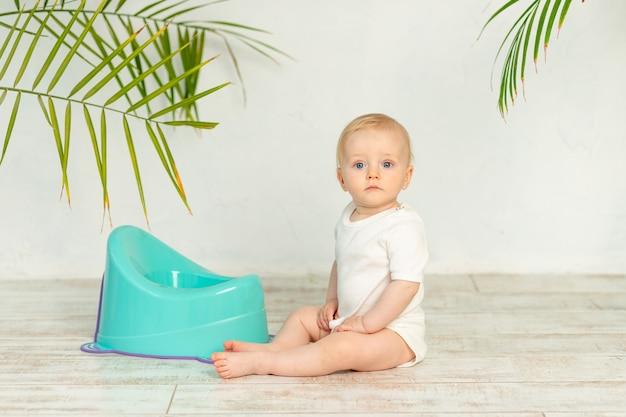 Blonde babyjongen in een witte bodysuit met een blauwe pot op de vloer van het huis