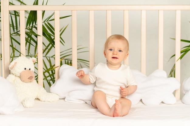 Blonde babyjongen met blauwe ogen in een witte bodysuit op een bed met katoenen ondergoed thuis voordat hij naar bed gaat