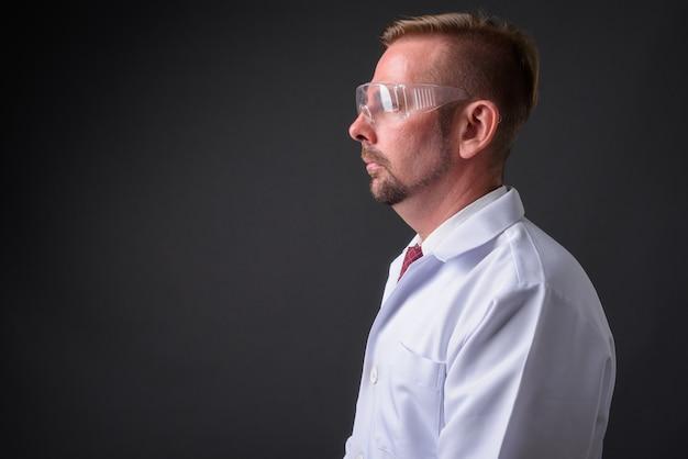 Blonde bebaarde arts met sikje tegen grijze muur