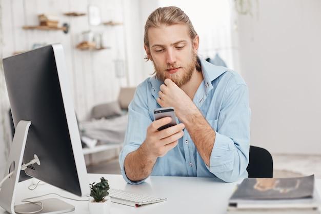Blonde, bebaarde mannelijke freelancer installeert nieuwe app op smartphone, downloadt programma op computer, gebruikt wifi, ontvangt bericht van partner. business, moderne technologieën, communicatie