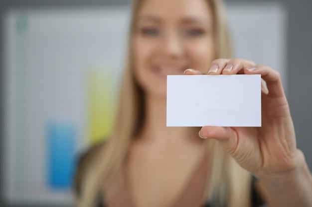Blonde bedrijfsvrouw die een adreskaartjehand houdt