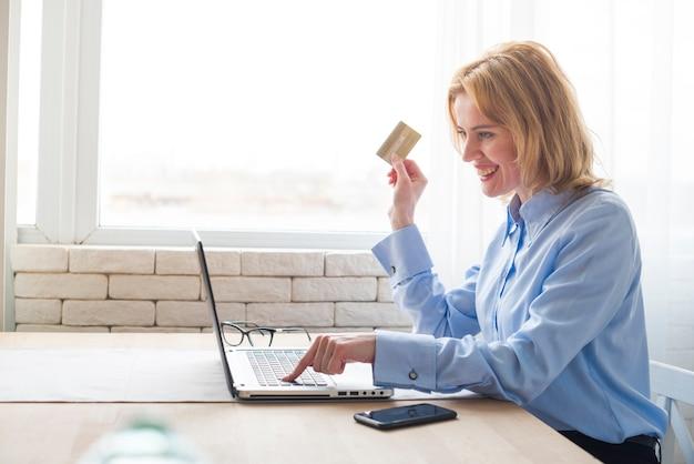 Blonde bedrijfsvrouw die laptop en creditcard gebruikt