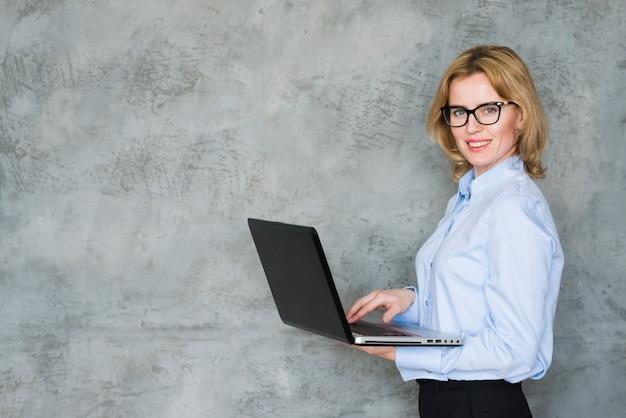 Blonde bedrijfsvrouw die laptop met behulp van