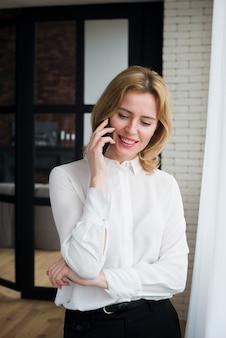 Blonde bedrijfsvrouw die op telefoon en het glimlachen spreekt