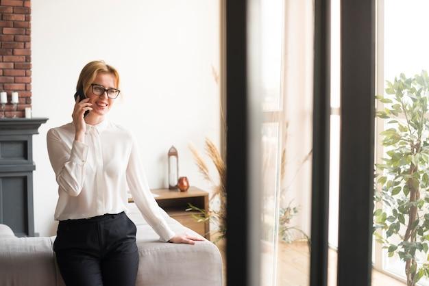 Blonde bedrijfsvrouw die op telefoon spreekt