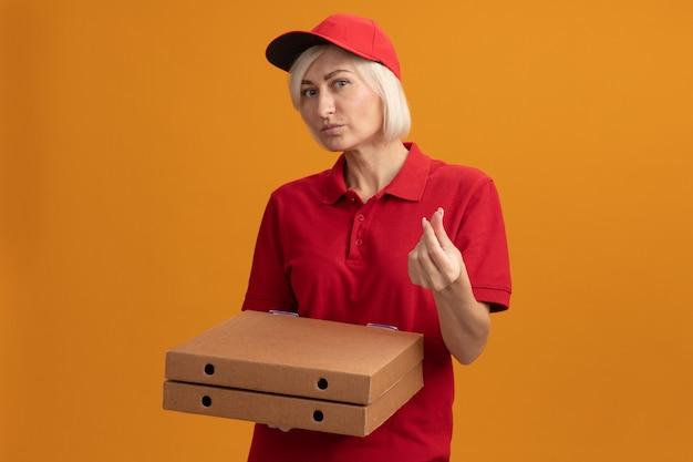 Blonde bezorger van middelbare leeftijd in rood uniform en pet met pizzapakketten die geldgebaar doen geïsoleerd op een oranje muur met kopieerruimte