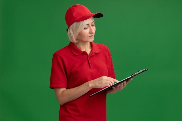 Blonde bezorgingsvrouw van middelbare leeftijd in rood uniform en pet houden en kijken naar klembord vinger erop zetten geïsoleerd op groene muur met kopieerruimte