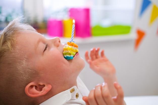 Blonde blanke jongen heeft plezier en houdt een stuk verjaardag regenboogcake met een brandende kaars in zijn mond op verjaardagsfeestje. feestelijke kleurrijke achtergrond