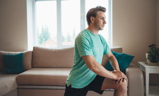 Blonde blanke man heeft een fitness-sessie thuis in sportkleding
