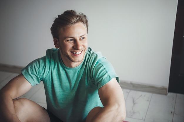 Blonde blanke man met sportkleding lacht tijdens het rusten na het doen van huisgymnastiekoefeningen