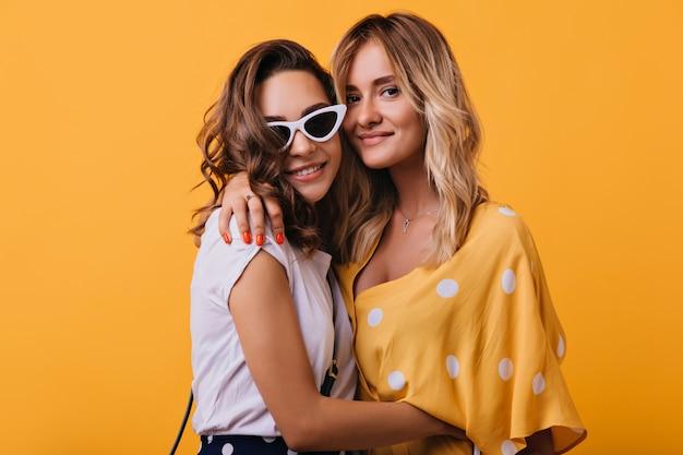 Blonde blanke meisje omhelst donkerharige vriend op geel. indoor portret van debonair brunette dame in vintage witte zonnebril.