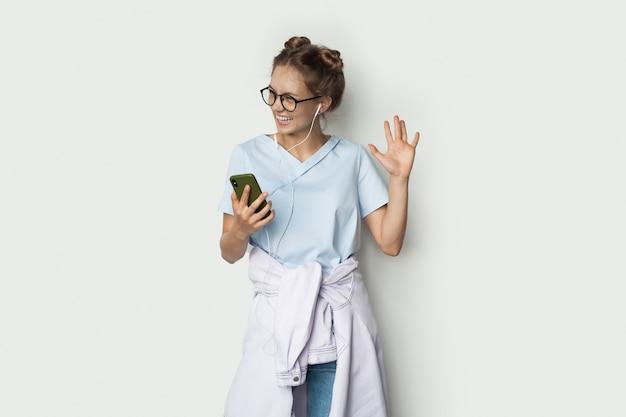 Blonde blanke vrouw gebaart hallo teken op een witte studiomuur terwijl ze naar muziek luistert en een telefoon vasthoudt