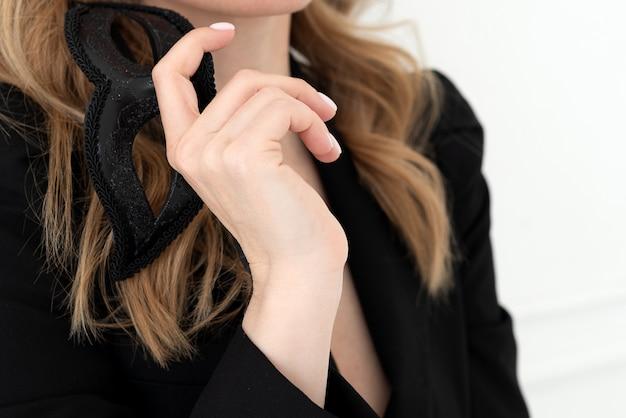 Blonde blanke vrouw houdt zwart carnavalsmasker in haar hand