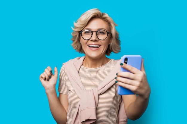 Blonde blanke vrouw met bril houdt een telefoon vast en kijkt naar de camera terwijl ze op een blauwe muur met vrije ruimte poseert