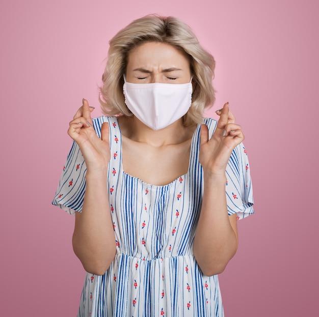 Blonde blanke vrouw met medisch masker op gezicht die een zomerjurk draagt, gebaart het droomteken op een roze studiomuur