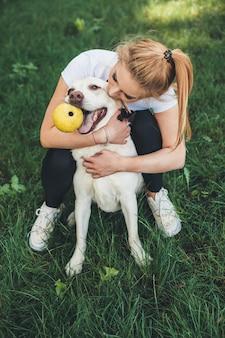 Blonde blanke vrouw omhelst haar hond tijdens het spelen in een groen park met een bal