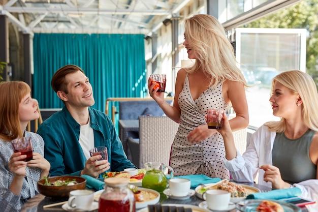 Blonde blanke vrouw zegt een toast ter ere van de verjaardag van een vriend