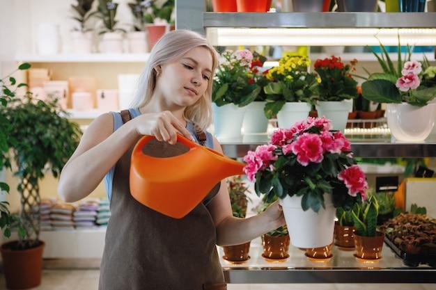 Blonde bloemist vrouw water, zorgt voor planten in de werkruimte van een bloemenwinkel