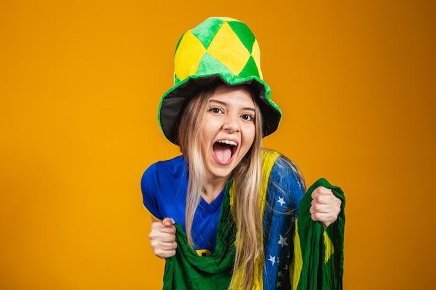 Blonde braziliaanse fan viert op gele achtergrond met braziliaanse vlag