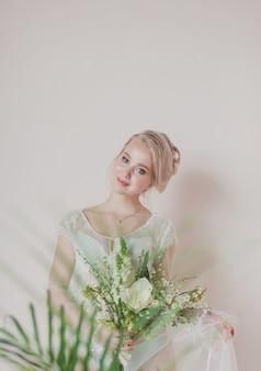 Blonde bruid bedrijf boeket. bruiloft interieur. huwelijksfotografie. portret van een schattige bruid.