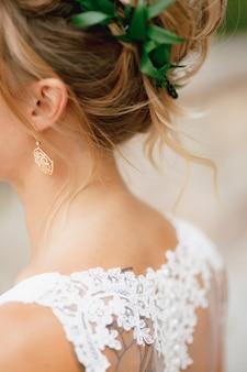 Blonde bruid in een kanten jurk met een sierlijke oorbel in haar oor en een olijfkrans