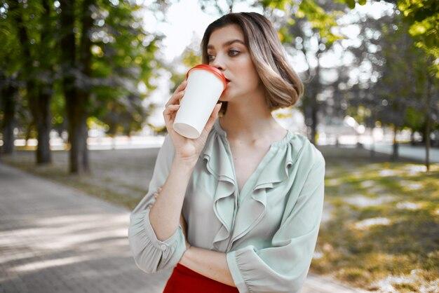 Blonde buiten in het park een kopje koffie vrije tijd levensstijl