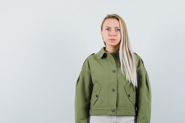 Blonde dame die camera in jasje, broek bekijkt en onrustig, vooraanzicht kijkt.