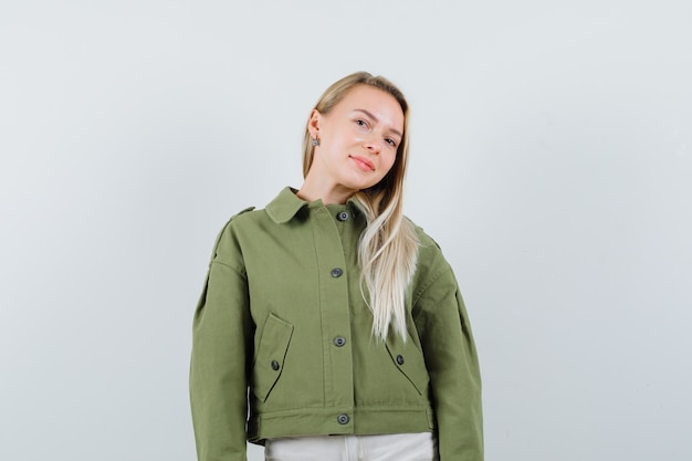Blonde dame die camera in jasje, broek bekijkt en verleidelijk, vooraanzicht kijkt.