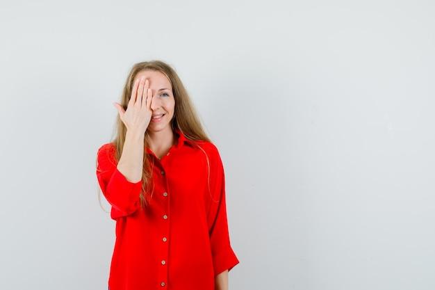 Blonde dame die één oog bedekt met hand in een rood shirt en er opgewonden uitziet,