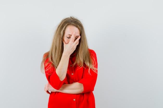 Blonde dame die hand op gezicht in rood overhemd houdt en verdrietig kijkt,