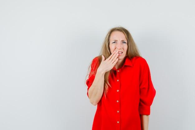 Blonde dame die hand op mond in rood overhemd houdt en sorry kijkt.