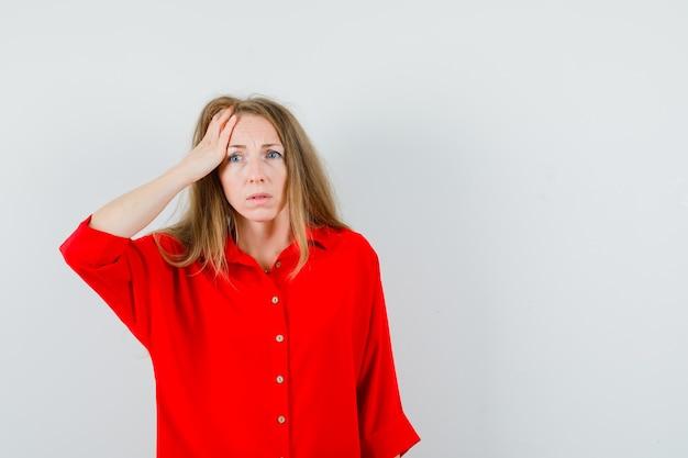 Blonde dame die hand op voorhoofd in rood overhemd houdt en verward kijkt.