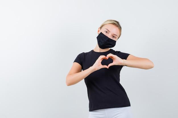 Blonde dame die hartgebaar in zwart geïsoleerd t-shirt toont showing