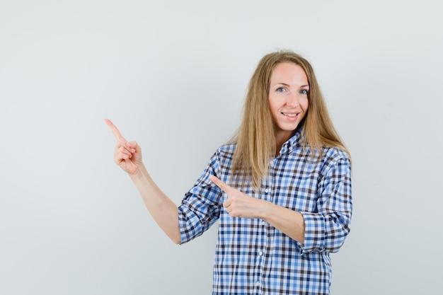 Blonde dame die naar de linkerbovenhoek in overhemd wijst en vrolijk kijkt.