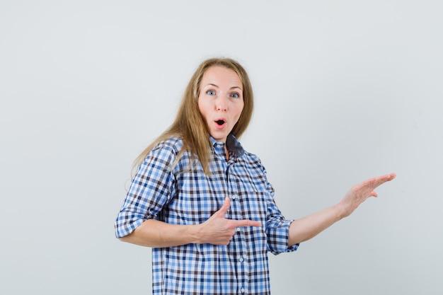 Blonde dame die naar de zijkant wijst, de handpalm opheft in het shirt en er verbaasd uitziet,