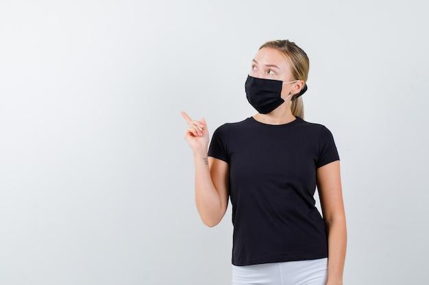 Blonde dame die omhoog wijst in een zwart t-shirt, een zwart masker en er attent geïsoleerd uitziet
