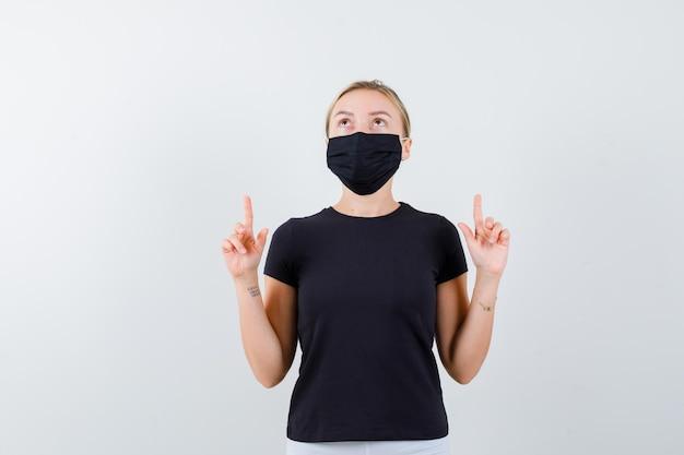 Blonde dame die omhoog wijst in een zwart t-shirt, een zwart masker en er voorzichtig geïsoleerd uitziet