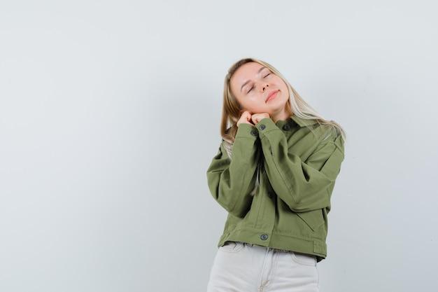 Blonde dame die op handen als hoofdkussen in jasje, broek leunt en er schattig uitziet. vooraanzicht.