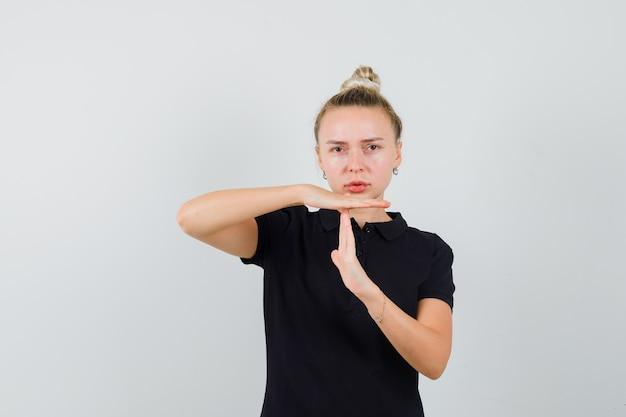 Blonde dame die tijdpauze gebaar in zwart t-shirt toont en ernstig kijkt. vooraanzicht.