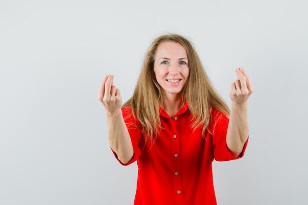 Blonde dame doet geldgebaar in een rood overhemd en kijkt vrolijk,