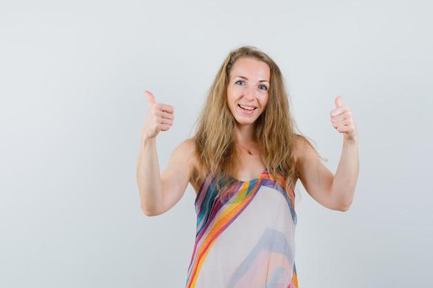Blonde dame dubbele duimen opdagen in zomerjurk en op zoek vrolijk