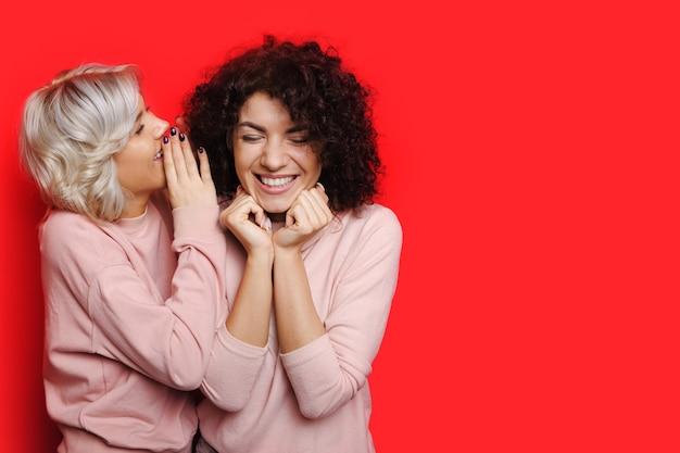 Blonde dame fluistert iets tegen haar vriendin met krullend haar terwijl ze op een rode muur met vrije ruimte poseert