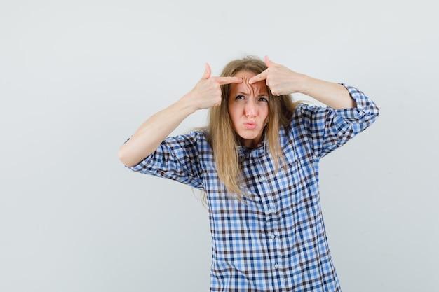 Blonde dame haar puistje op voorhoofd in shirt knijpen
