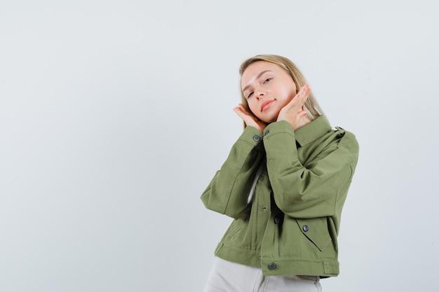 Blonde dame hand in hand in de buurt van wangen in jas, broek en schattig op zoek. vooraanzicht.